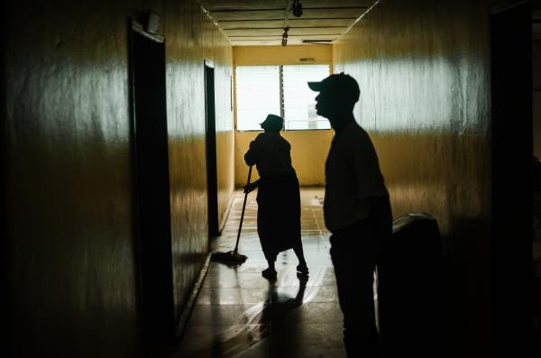 A cleaner mops a dimly lit corridor.