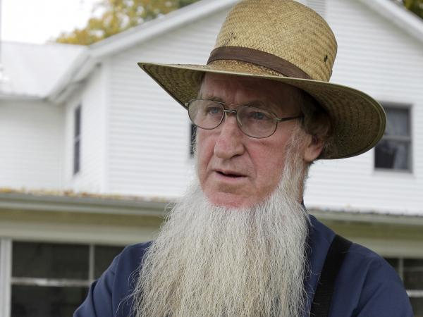 Sam Mullet stands in the front yard of his home in Bergholz, Ohio, in 2011. Mullet's conviction for hate crimes for cutting the hair and beards of fellow members of his faith was overturned Wednesday.