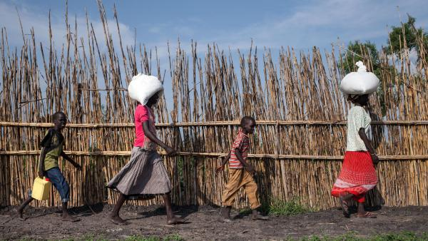 Martha Nyarueni (right) and her family return to their home outside the town of Leer, South Sudan, after receiving an aid package in early July. The country is facing serious food shortages, but it has not formally been declared a famine.