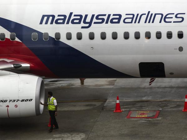 A Malaysia Airlines crew member inspects an airplane at Kuala Lumpur International Airport on Thursday. The carrier announced it was laying off a third of its workforce amid steep financial losses.
