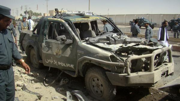 An Afghan police officer looks at a police vehicle damaged in a suicide attack Tuesday in Lashkar Gah, Helmand province.