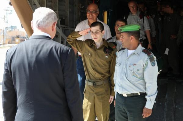 <p>Israeli soldier Gilad Shalit (center) salutes Israeli Prime Minister Benjamin Netanyahu (left) after arriving by helicopter at the Tel Nof airbase near Tel Aviv on Tuesday.</p>