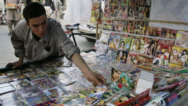 When the Taliban ruled Afghanistan, CDs and DVDs were forbidden. Now the Taliban are trying to attract recruits and supporters by making their own CDs. Here an Afghan man arranges DVDs for sale in the southern city of Kandahar in 2008.