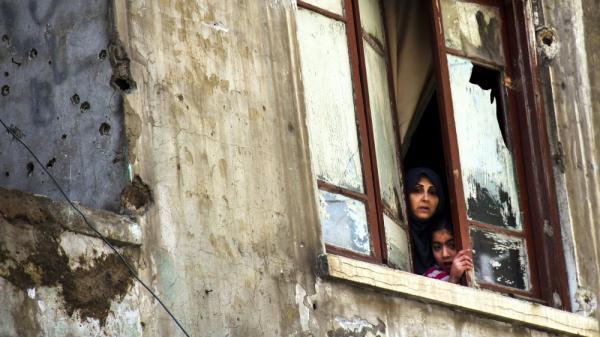 The fighting in Syria was seen as a spark for clashes in the Lebanese city of Tripoli last week. Here a Lebanese woman and her daughter look out the window of their bullet-pocked home in Tripoli on Sunday, Feb. 12.