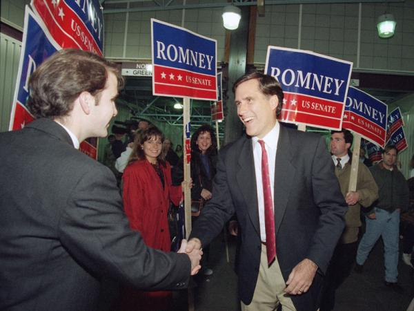 Then a Republican candidate for the U.S. Senate, Mitt Romney shakes the hand of a commuter while campaigning at North Station in Boston on Nov. 7, 1994.