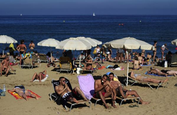People relax at a beach in Barcelona, Spain, on a Monday last summer. Many Spanish workers are upset that some traditional four-day holiday weekends might be scaled back to just three days.