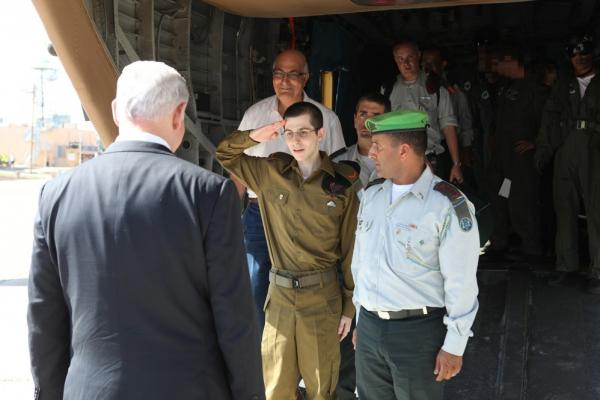 Gilad Shalit salutes Israeli Prime Minister Benjamin Netanyahu at the Tel Nof air base after being held captive for five years by Hamas.