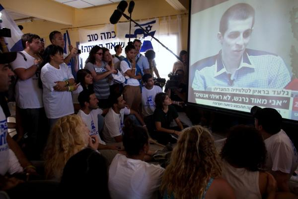 People in Mitzpeh Hila watch the first televised images of the 25-year-old Shalit, who doctors said shows signs of malnutrition, following his release.