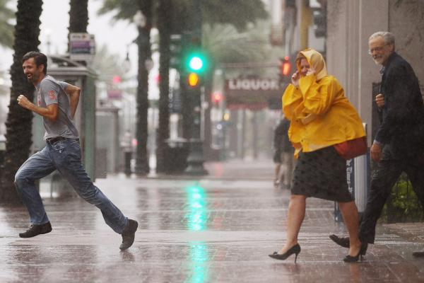 People make their way across Canal Street in New Orleans. Ed Rappaport, deputy director of the National Hurricane Center, said Isaac's core would pass west of the city and head for Baton Rouge.