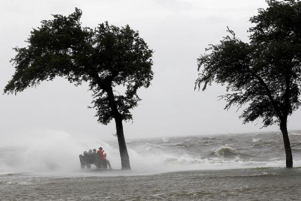 People sit on a bench along the seawall in the storm surge from Isaac, on Lakeshore Drive along Lake Pontchartrain, as the storm approaches landfall, in New Orleans, Tuesday, Aug. 28.