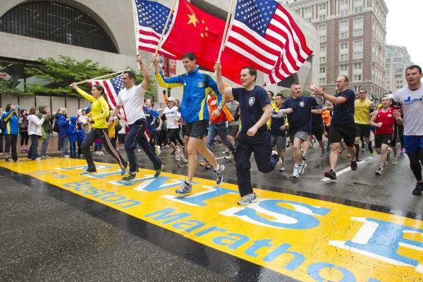 "Runners holding American flags and a Chinese flag cross the finish line after completing the final mile of the Boston Marathon course during ""#onerun"" in Boston, Massachusetts on Saturday."