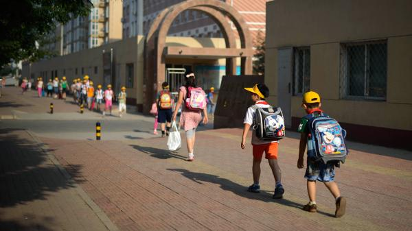 In the hopes of easing pressures on China's students, the country' education officials are considering a ban on written homework. Here, students walk to school in Beijing in June.