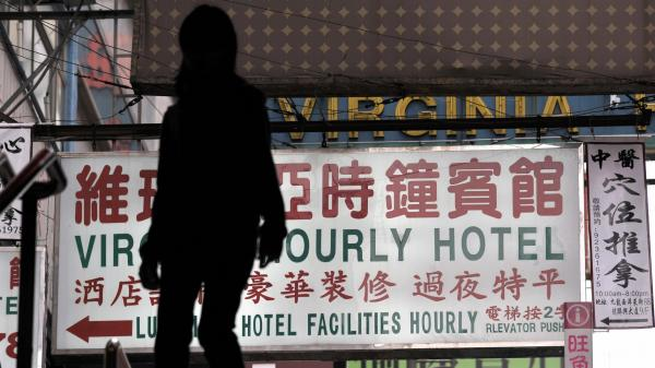 "A passerby walks past a sign for an ""hourly hotel"" in a popular shopping district in Hong Kong. An recent anti-vice crackdown in China has targeted mistresses and sex workers as part of a social problem."