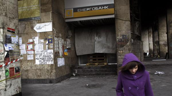 A woman walks past a local bank in Kiev's Independence Square that was set on fire during Ukraine's recent unrest. The country is now squeezed by IMF-mandated austerity measures and the specter of higher prices for gas from Russia.