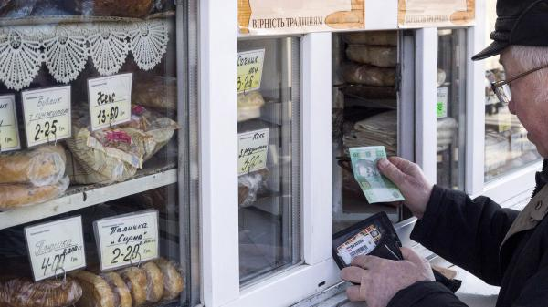A customer pays for goods at a street kiosk in Kiev on Feb. 26.
