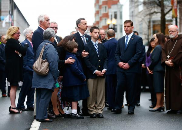The family of Martin Richard, who was killed in the Boston Marathon bombing one year ago today, gather with Boston mayor Marty Walsh, Archbishop of Boston Sean O'Malley and other victims' family members and bombing survivors during a wreath-laying ceremony on Boylston Street near the finish line. (Jared Wickerham/Getty Images)