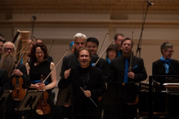 Seattle Symphony Music Director Ludovic Morlot stands before his orchestra just before their Spring for Music concert at Carnegie Hall, Tuesday, May 6, 2014. (Inspired by the oceanic theme of the concert, the musicians wear blue scarves and ties created by Seattle fashion designer Michael Cepress.)
