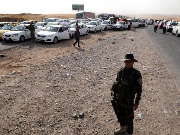 Thousands of Iraqis fleeing Sunni extremists fled to the Kurdish city of Erbil, where they lined up here on June 12 at a checkpoint before entering.