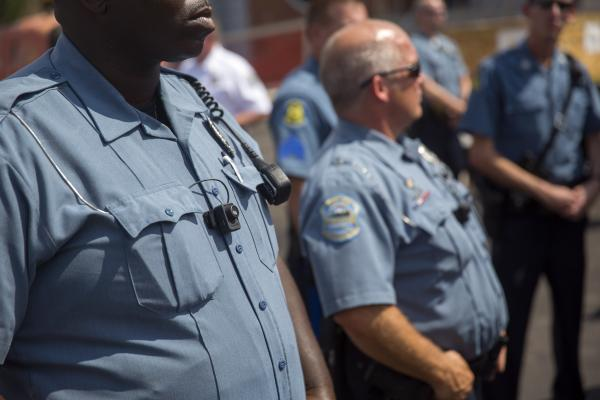 Members of the Ferguson Police Department wear their new body cameras during a rally Saturday in Ferguson, Mo.
