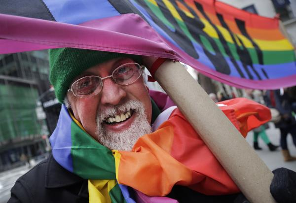 "Artist Gilbert Baker, designer of the Rainbow Flag, is draped with the flag while holding a banner that reads ""Boycott Homophobia"" before the start of the St. Patrick's Day parade in March in New York."