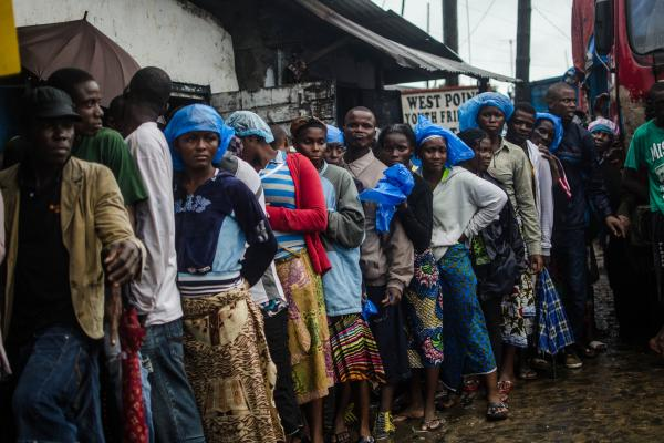 Recovering from the toll of the Ebola quarantine, residents of the West Point slum in Monrovia line up for food.