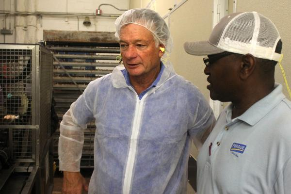 At left, CEO Jim Perdue, with hatchery manager David Bailey, inside the company's hatchery in Salisbury, Md.