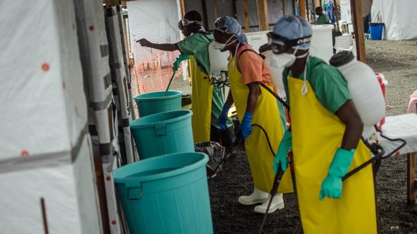 Workers wait to spray disinfectant on medical staff after they treat Ebola patients at a clinic run by Doctors Without Borders, in Monrovia, Liberia.