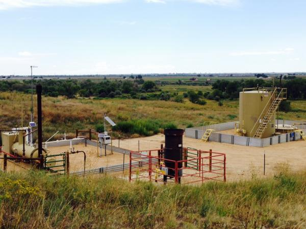 An oil and gas site near the St. Vrain Creek. Metal berms replace earthen ones.