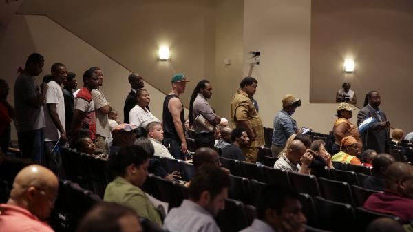 A line of people wait to speak during a meeting of the Ferguson City Council on Tuesday. The meeting was the first for the council since the fatal shooting of Michael Brown by a city police officer.