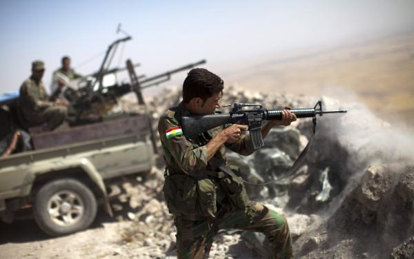 An Iraqi Kurdish peshmerga fighter fires at Islamic State militants from his position on Mount Zardak, Iraq, on Tuesday. Kurdish forces in northern Iraq have worked with the U.S. military, which has been bombing Islamic State positions from the air.