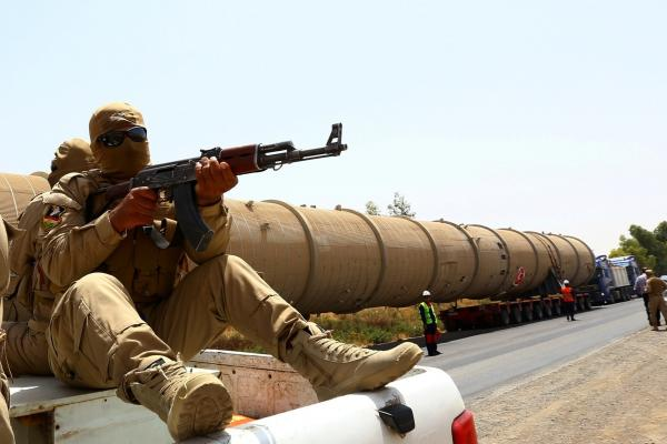 A soldier guards a pipe en route to the Kawergosk Refinery near Irbil, the capital of the autonomous Kurdish region of northern Iraq, in July. Fighting in northern Iraq forced the closure of the country's largest oil refinery, Baiji, and cut production from the Kirkuk oil field this summer.