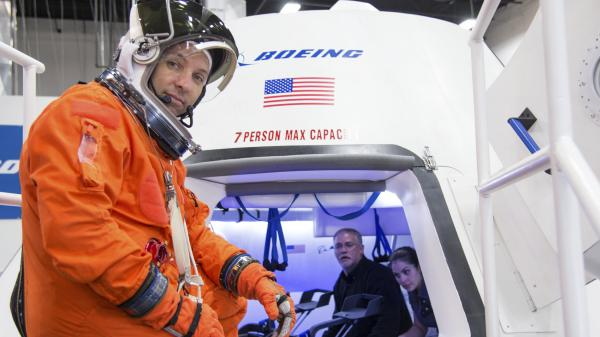 In an image provided by NASA, astronaut Randy Bresnik prepares to enter Boeing's CST-100 spacecraft for an evaluation at the company's Houston Product Support Center. NASA awarded Boeing with a $4.2 billion contract Tuesday.