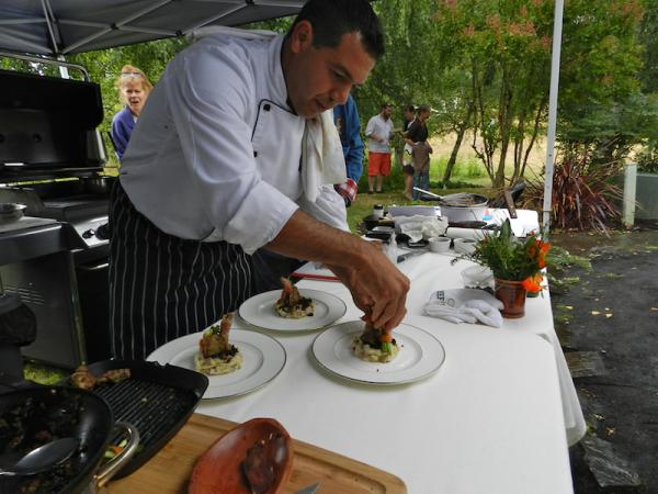 Chef Hamid Serdani serves a feral pig chop on a bed of mashed potatoes and sauteed dandelion greens with a blackberry balsamic curry sauce at the 2013 edition of the invasive species cook-off.