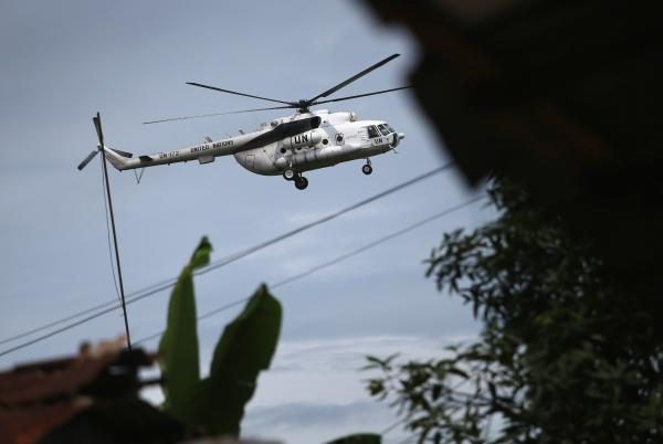 A United Nations helicopter flies overhead as a burial team collects the body of a woman suspected of dying of Ebola in Monrovia, Liberia, in August.