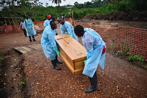 In Sierra Leone, a burial team from the government carries the coffin of an Ebola doctor who succumbed to the virus. Funerals and other expressions of mourning are key moments for anthropologists to translate between native cultures and foreign aid efforts, anthropologist Ann Kelly says.