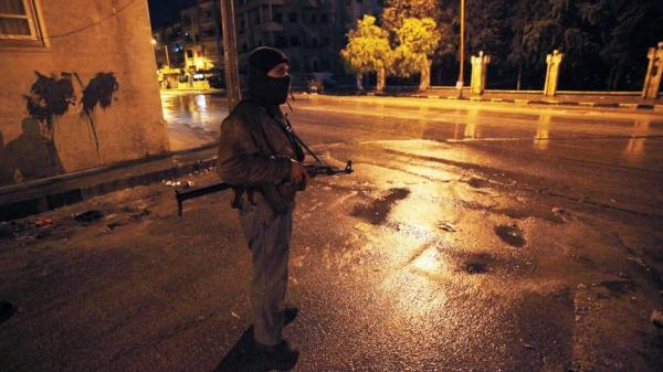 A Syrian rebel stands guard at a street in Idlib, Syria, Wednesday, Feb. 8, 2012.