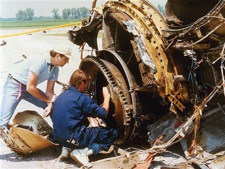 National Transportation Safety Board investigators check over the burnt remains of a jet engine from the DC-10.