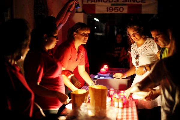 Workers serve pizza by candlelight outside Filippi's Pizza Grotto in San Diego's Little Italy neighborhood. Power had been restored in much of the city by early Friday.