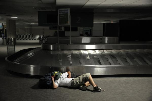A stranded passenger sleeps in the baggage claim area at San Diego International Airport, where outgoing flights were temporarily grounded.