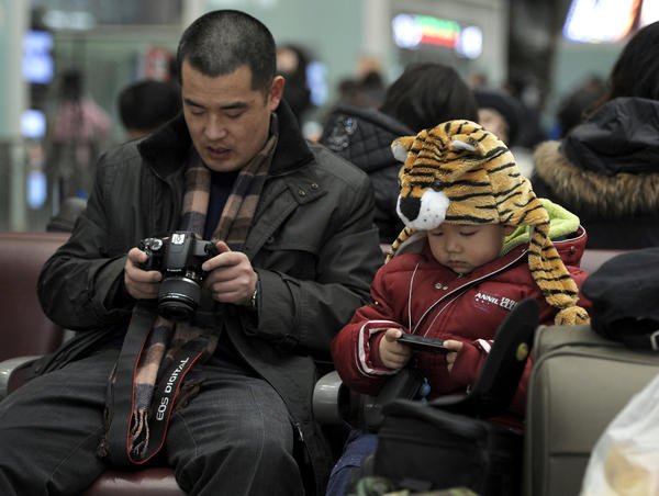 A man and his child check out photos they took while waiting to board trains at the south train station in Beijing, in February 2010.