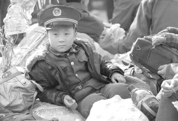 A Chinese boy wearing a People's Liberation Army uniform sits on his family's belongings while waiting for a train at the crowded Beijing railway station in December 1992.
