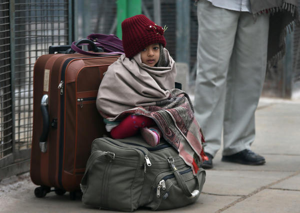 An Indian girl sits on her family's luggage as she waits for a train at a railway station in New Delhi, India, in January 2013.