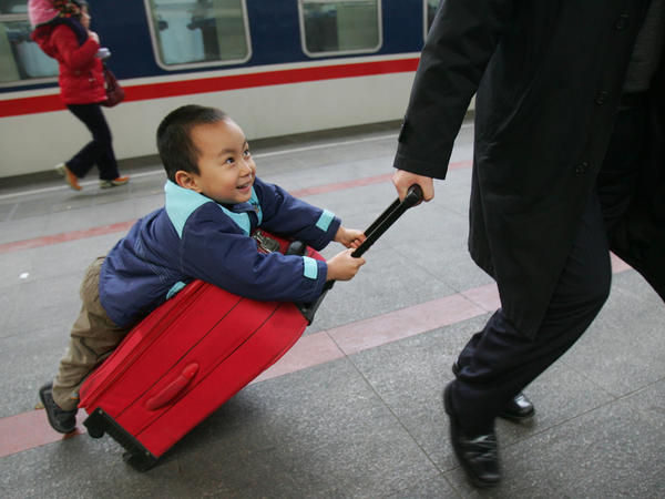 A boy hitches a ride on a suitcase as he waits to board a train at Beijing West Railway Station during Chunyun travel peak on Feb. 8, 2007.
