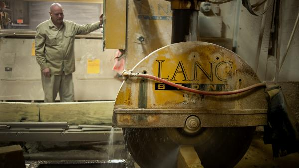 An employee uses a wet saw to cut a slab of sandstone at a Lang Stone Co. facility in Columbus, Ohio, in January. Using water while cutting helps keep dust out of the air.