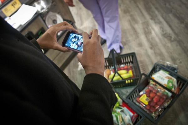Nyuma Harrison photographs the groceries she purchased. She will share the images with her teammates.
