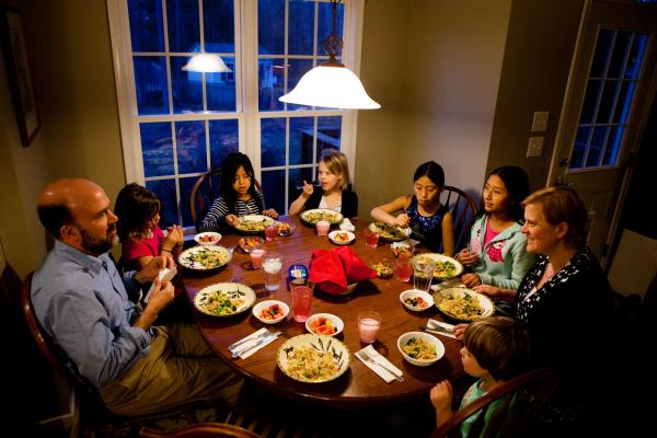 The Brown-Spencer family gathers for dinner at their home in Mechanicsville, Va. This family of eight manages to eat together nearly every weeknight, but they've had to cut back on many after-school activities to make it work. From left: Doug Brown, Laura, Celedonia, Anna, Miriam, Anita, Amy Spencer and Gavin.