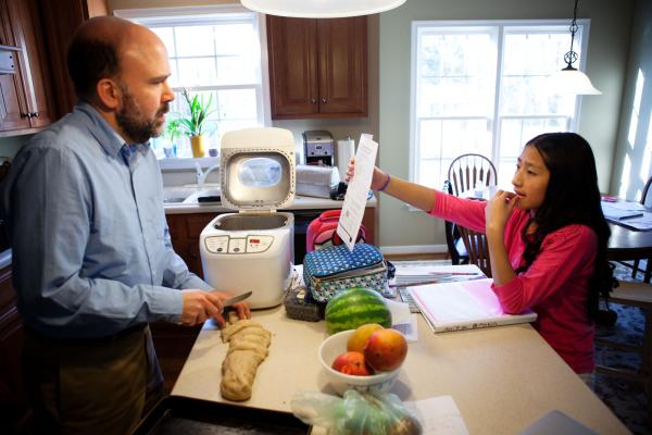 Brown makes dinner rolls while helping his seventh-grader, Anita, with math homework.
