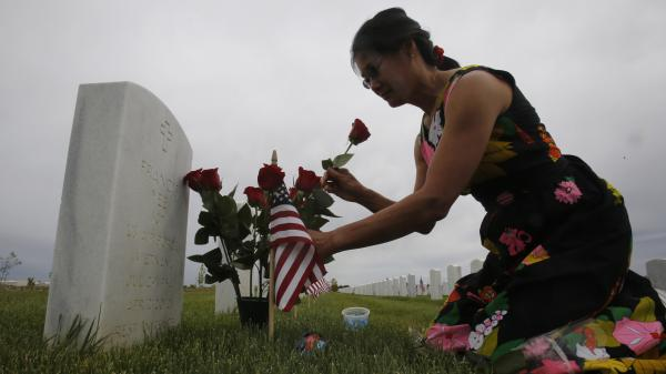 Karen Jang places flowers on the the grave of her late boyfriend, Vietnam veteran Francis Yee, during her Memorial Day visit to the Sacramento Valley National Cemetery, in Dixon, Calif.
