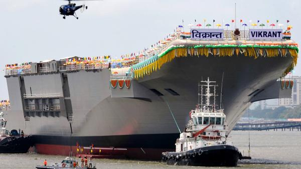 Tugboats guide the INS Vikrant as it leaves the Cochin Shipyard after a launch ceremony in Kochi, India, on Monday. When it comes into full service in 2018, India will become the fifth nation to have designed and built its own aircraft carrier.
