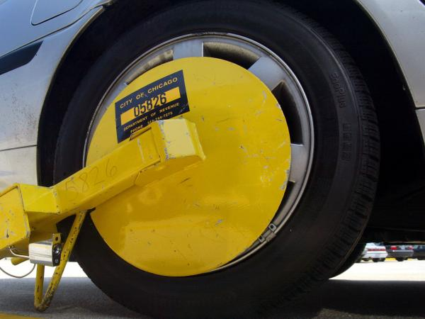 "A ""Denver Boot"" wheel lock attached to a car in a parking lot at O'Hare International Airport in Chicago."